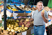 Adult man is choosing potato in the vegetables store