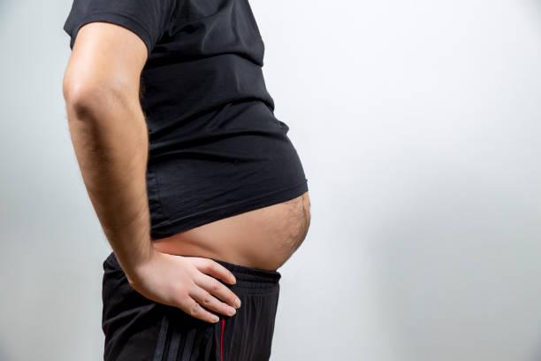 erwachsener mann zeigt seine fett, unhealty bauch - blähbauch medikamente stock-fotos und bilder