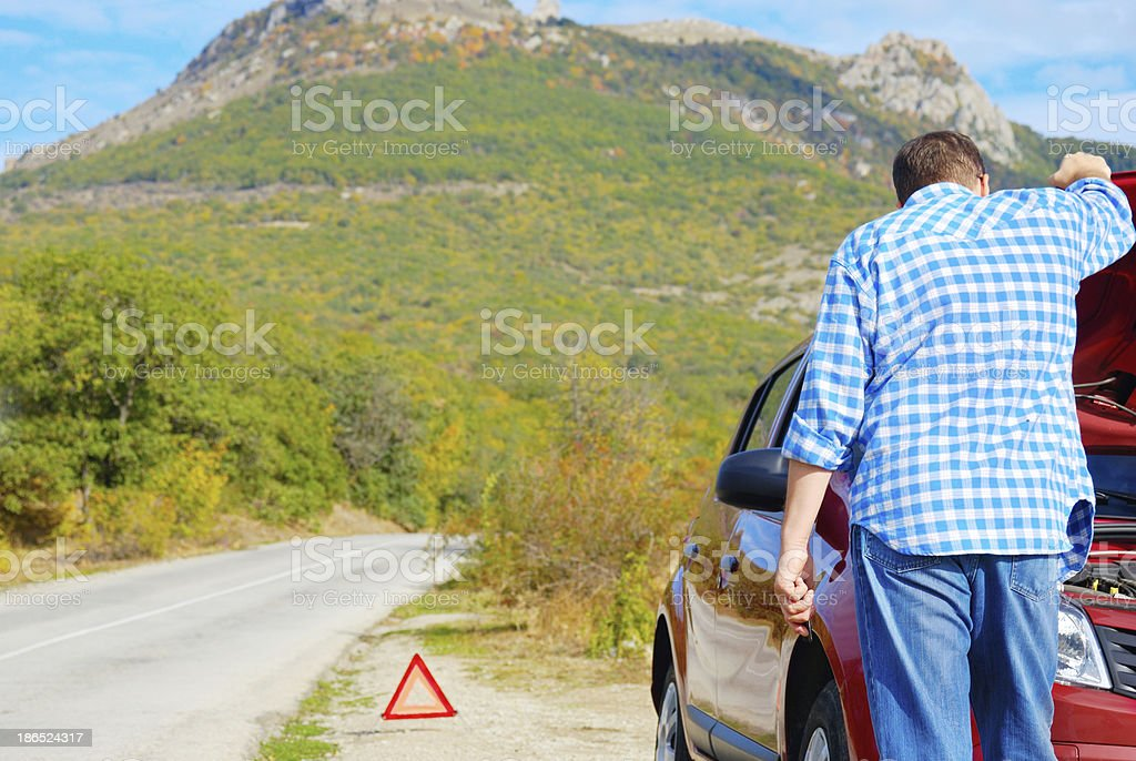 Adult man is standing near his broken car royalty-free stock photo