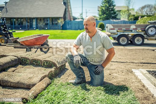 Adult man laying sod for new lawn. He is taking a small brake after working hard