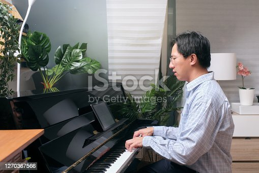Adult man learning to play piano using digital tablet with an online lesson and course in living room at home, Happy Asian businessman relaxing by playing piano, Reduce stress with music concept