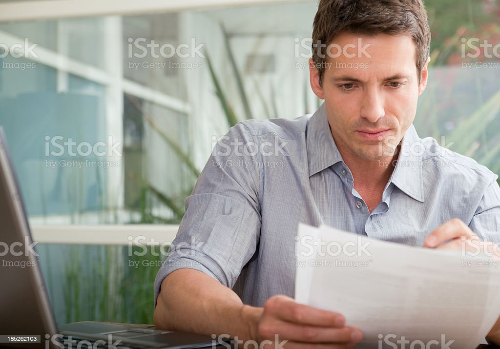 Adult man looking over papers stock photo