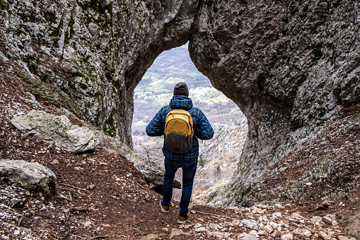 Adult Man Looking Through Natural Window Formed in Rock Near Otlica Village in Slovenia