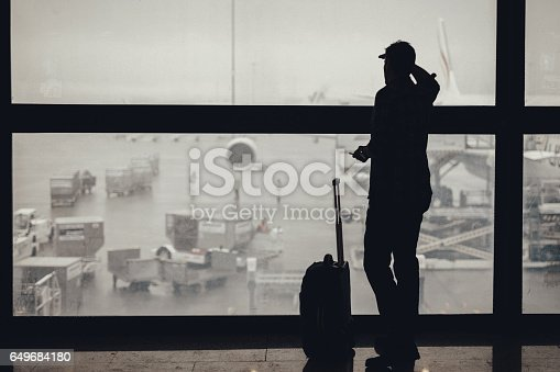 509630674 istock photo Adult man looking through the window at the airport 649684180