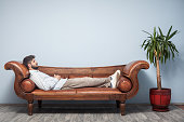 Adult Man Lying Down On Psychiatrist Couch