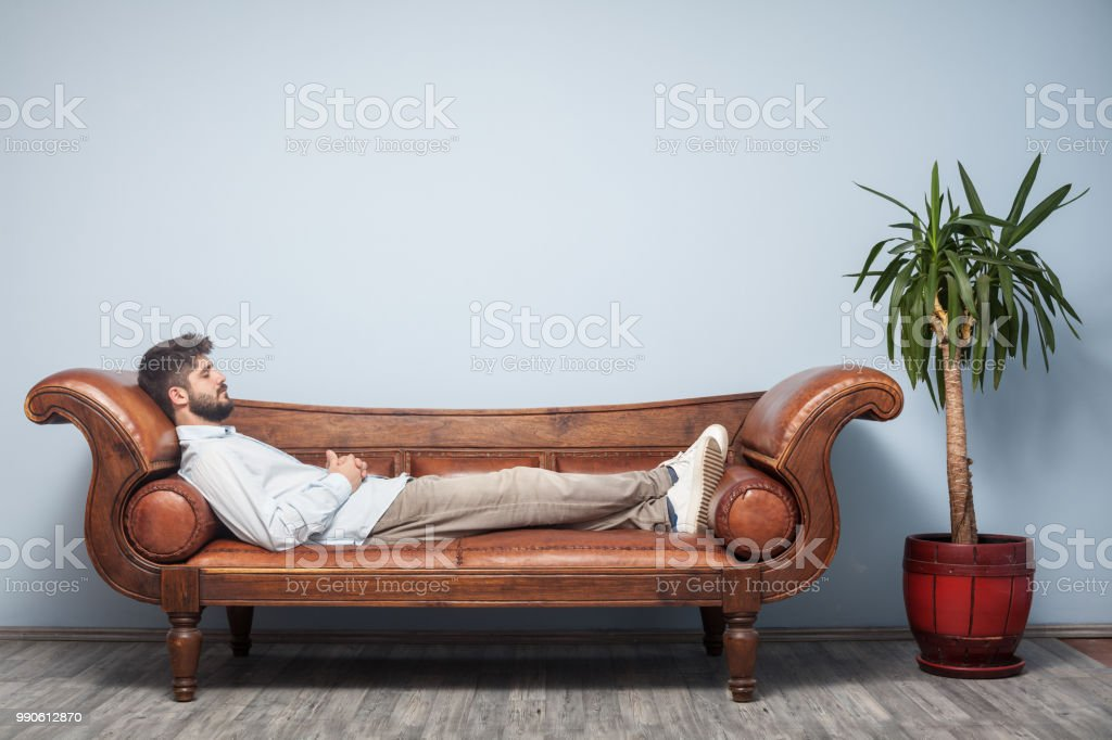 Adult Man Lying Down On Psychiatrist Couch stock photo