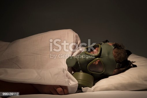 istock Adult man lying in bed in white sheets with eyes closed, wearing gas mask 996439112