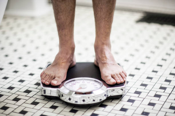 Adult man on bathroom scales. stock photo