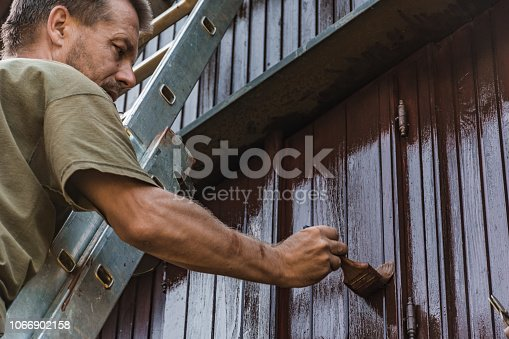 Adult Man Painting an Old House With Protective Paint.