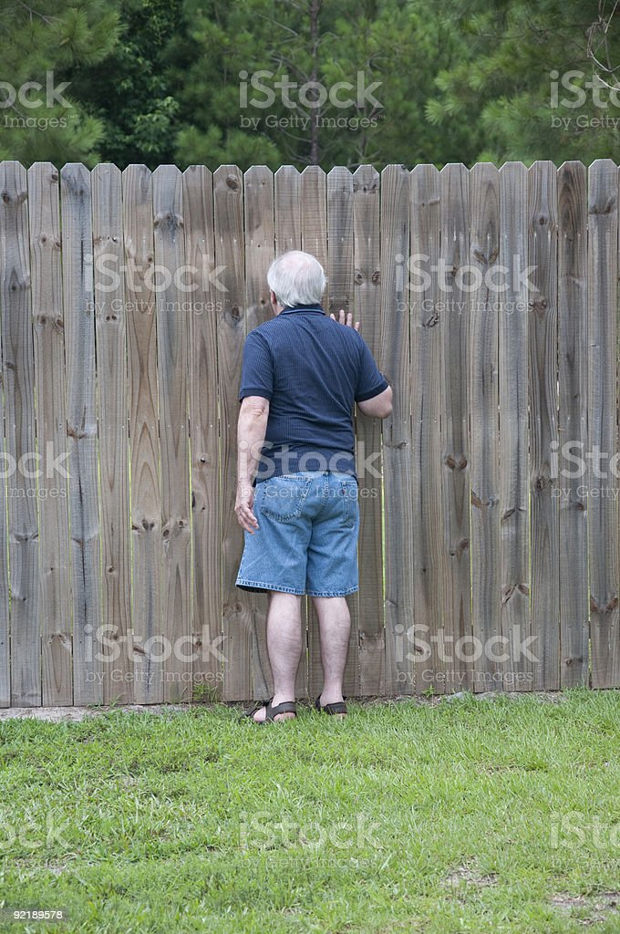 Adult Man Peeking Through a Hole in the Fence royalty-free stock photo