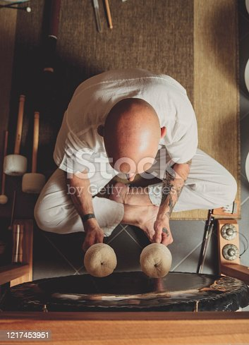Adult man playing gong
