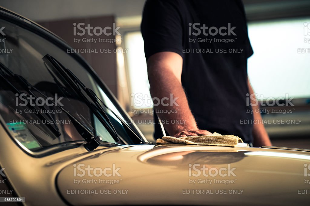 Adult man polishing oldtimer car in workshop with cleaning cloth stock photo