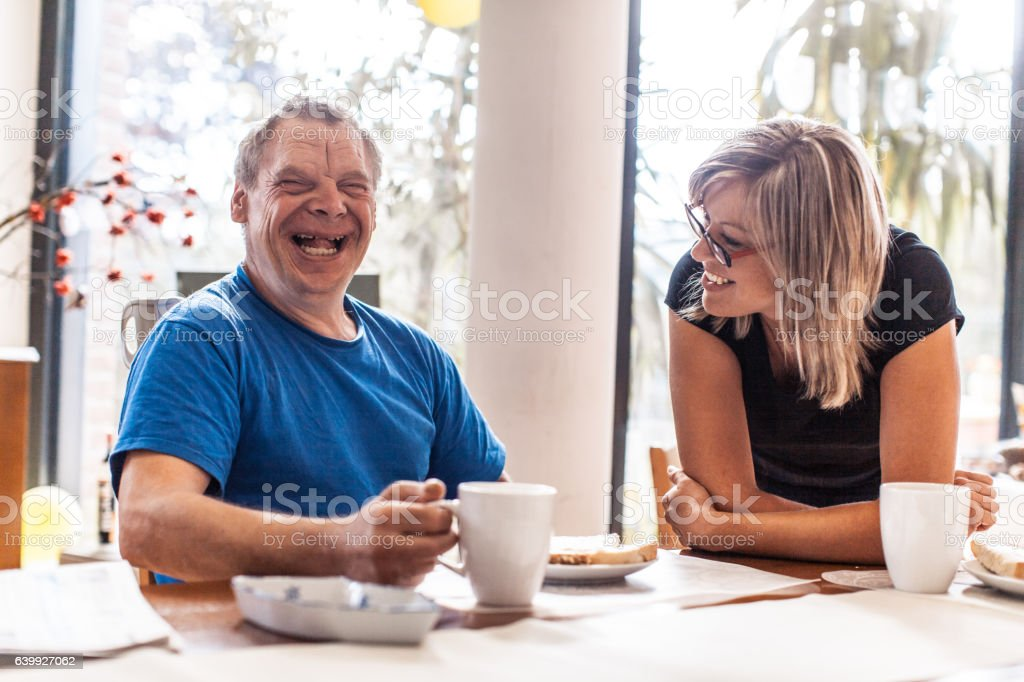 Adult Man Portrait with a Down Syndrome and a Caregiver - foto de stock