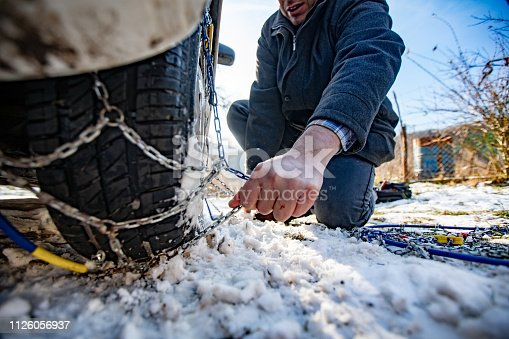 Adult Man Positioning Tire Chains on Car.