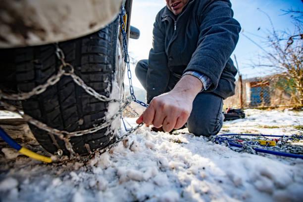volwassen man positionering tire chains op auto - tractieapparaat stockfoto's en -beelden