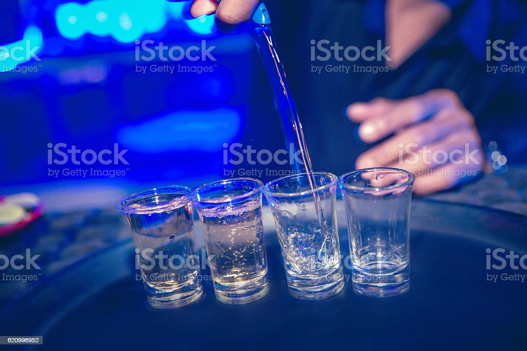 Adult man pouring tequila on the party stock photo