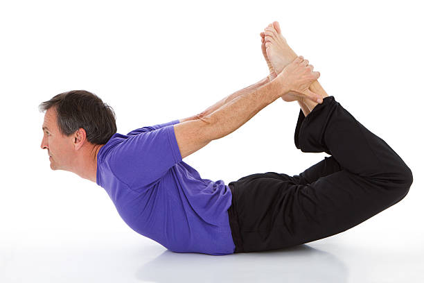 Adult man practicing yoga - dhanurasana pose stock photo
