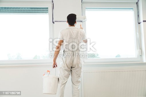 istock Adult man professional painter painting the room white 1167186798