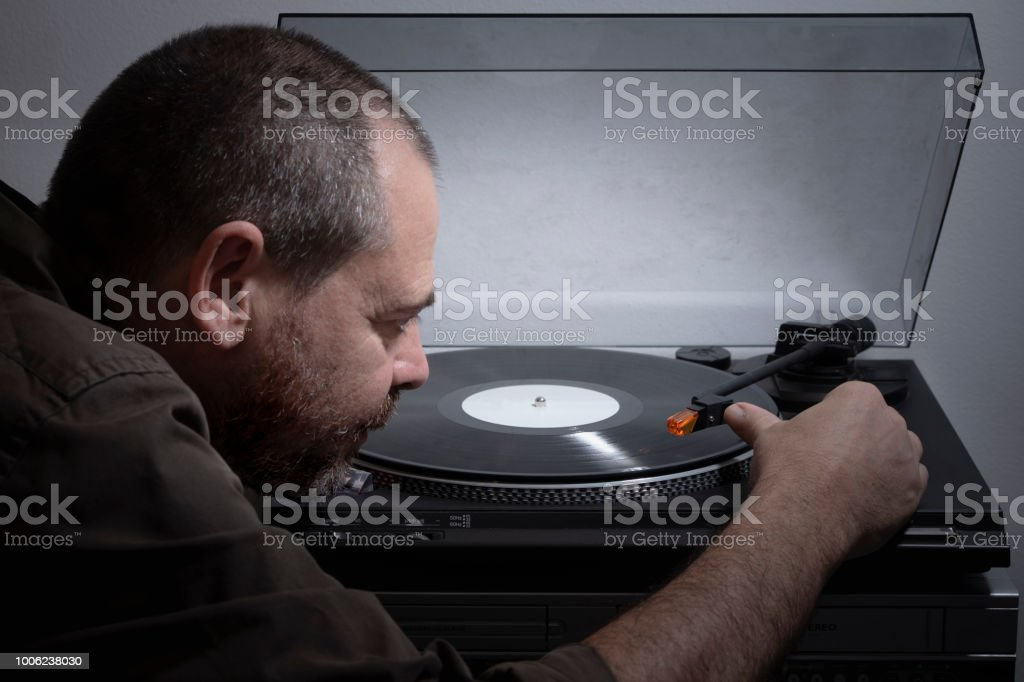 Adult man putting the cartridge record player on the vinyl - foto stock