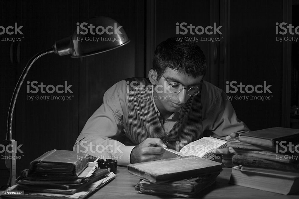 Adult man reading bible on table in the dark stock photo