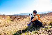 Adult Man Relaxing With His Dog in Remote Location Amongst Vineyards.