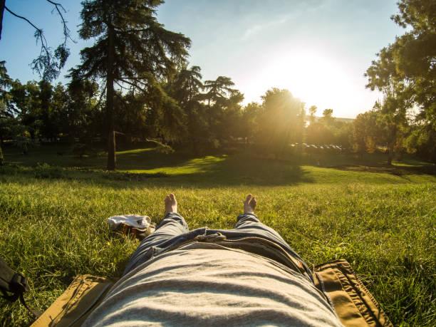 descansando en el parque con puesta de sol y Descalzas y un sombrero de hombre adulto - foto de stock