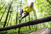 Adult Male Runner Jumping Across Fallen Down Tree.