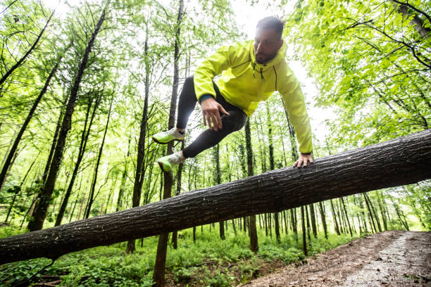 Adult Man Running in Forest in Bad Weather Adult Male Runner Jumping Across Fallen Down Tree. obstacle course stock pictures, royalty-free photos & images