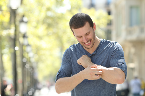 istock Adult man scratching itchy arm in the street 1180289109