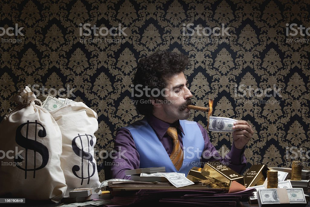Adult man sitting lighting cigar with burnt dollar bill stock photo