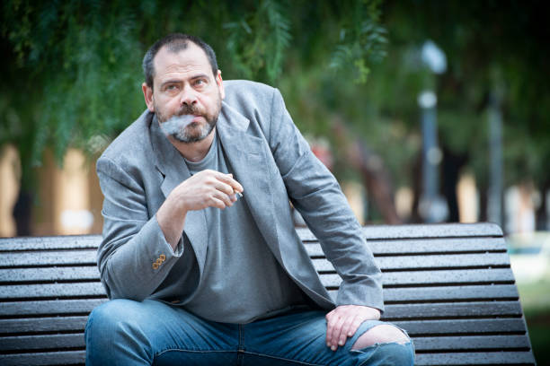 Adult Man sitting on a bench at public park smoke a cigarette - foto stock