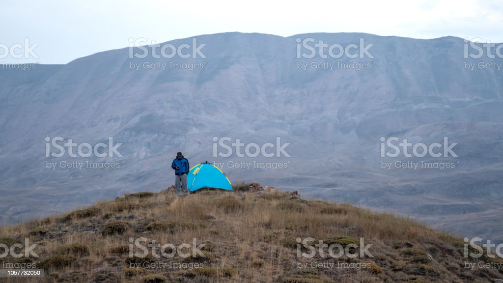 Adult Man Standing By Camping Tent On Top Of Hill stock photo