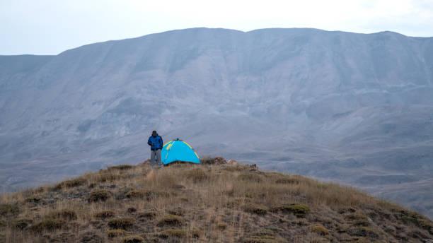 Hombre adulto por tienda de campaña en la cima de la colina - foto de stock