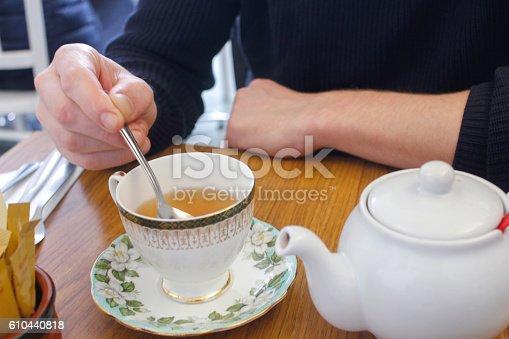 Adult man stirring hot tea