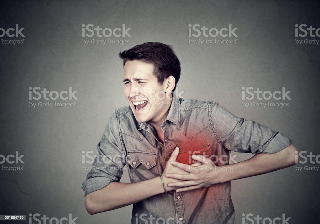 Adult man suffering from severe sharp heartache, chest pain. Heart disease concept - foto de stock