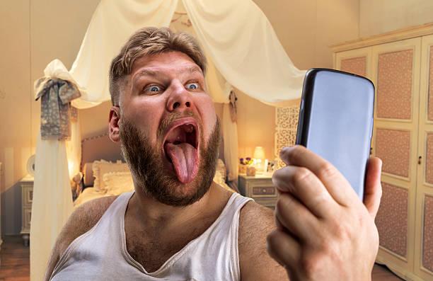 erwachsener mann nimmt selfie mit seinem zunge - ausgefallene mode für mollige stock-fotos und bilder