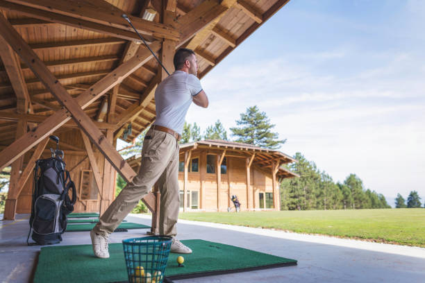 Adult man taking a tee shot at the golf school stock photo