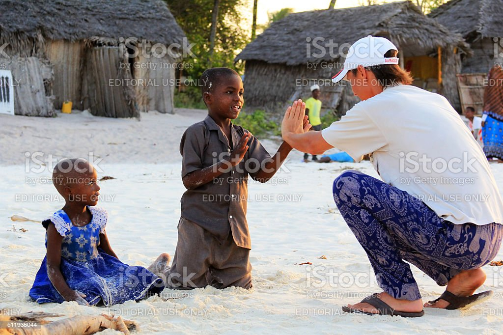 Adult man tourist plays with African children stock photo