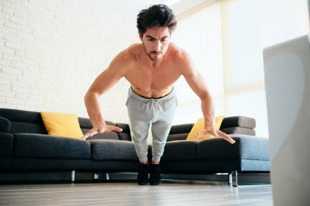 Adult Man Training Chest Muscles At Home Doing Explosive Push-Ups stock photo