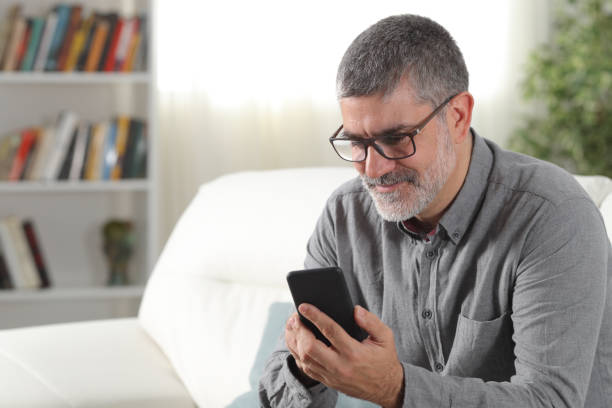 Adult man using a smart phone at home stock photo