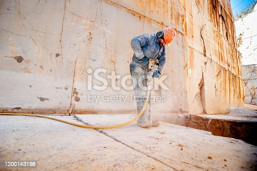 Adult Man Using Pneumatic Hammer in Marble Quarry.