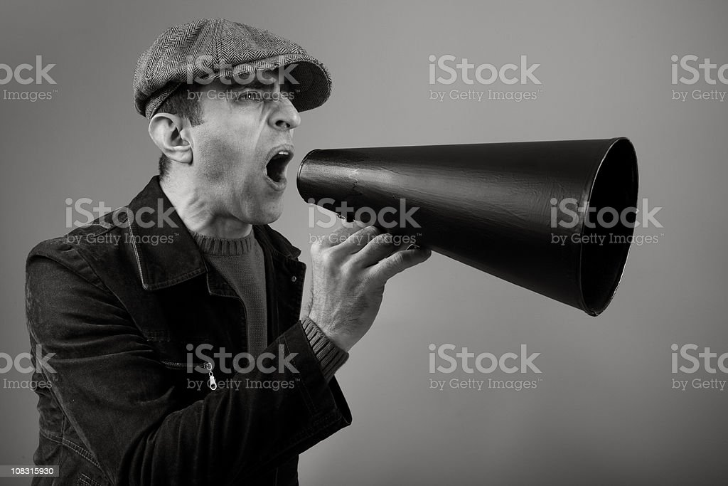 Adult Man Wearing Flat Cap Shouting On Old Fashioned Megaphone royalty-free stock photo