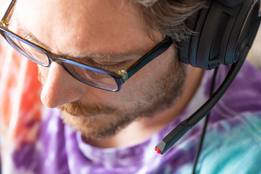 Adult Man Wearing Headphones with a Microphone Playing Online Video Game