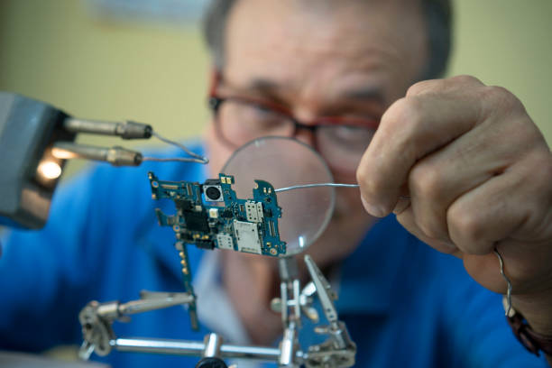 Adult man welding an electric circuit Adult man welding an electric circuit soldering iron stock pictures, royalty-free photos & images