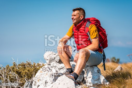 Mature adult caucasian man with back pack sitting on a rock in mountains and looking away.