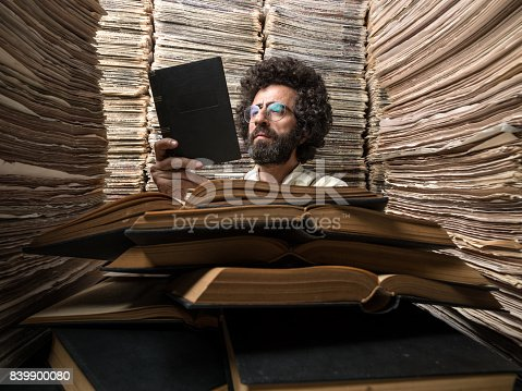 istock Adult Man With Dark Hair Reading Book In Printed Media Archive 839900080