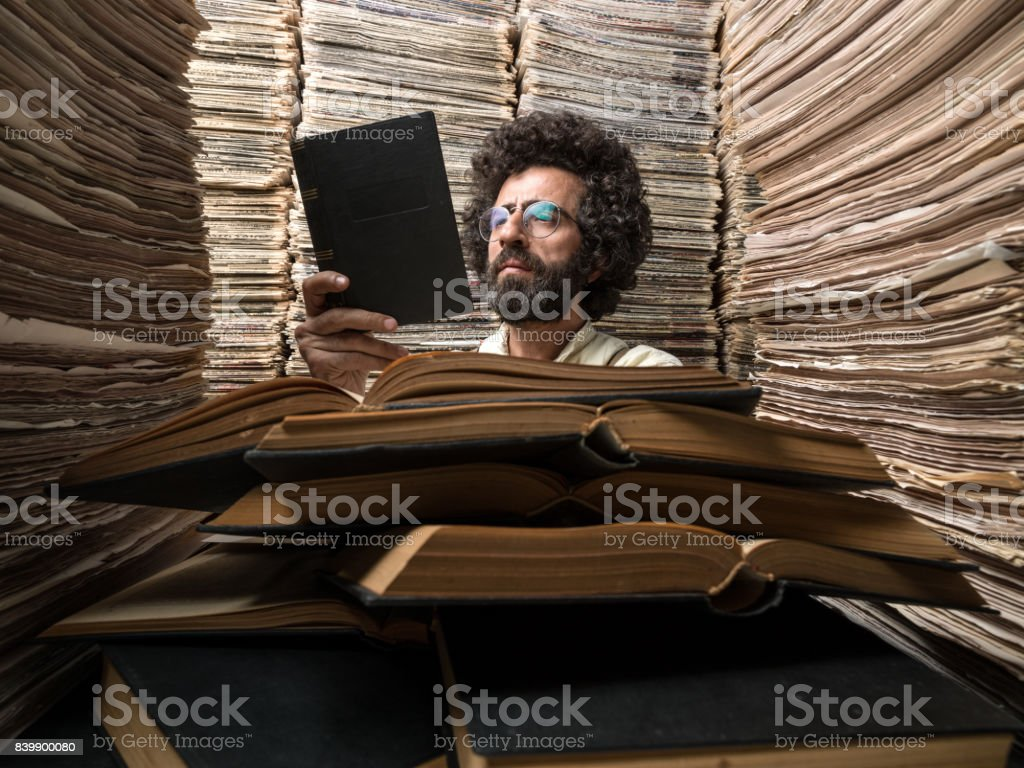 Adult Man With Dark Hair Reading Book In Printed Media Archive stock photo