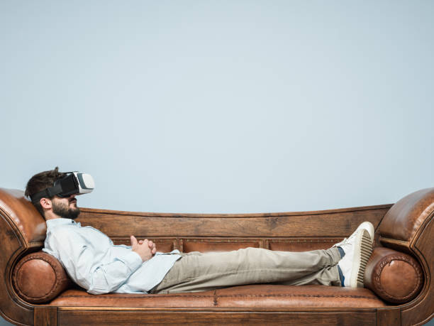 Adult Man With VR Headset Lying Down On Psychiatrist Couch stock photo