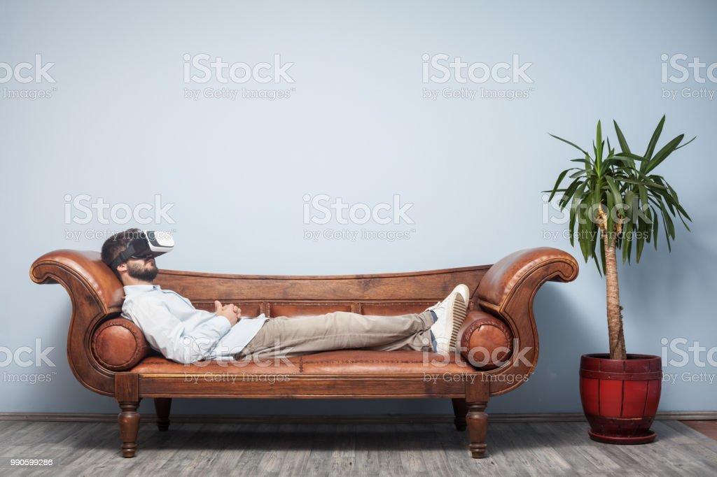 Erwachsener Mann mit VR Kopfhörer auf der Psychiater-Couch liegend – Foto