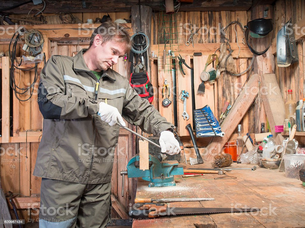 Adult man work clothes and gloves cost around wooden table foto royalty-free
